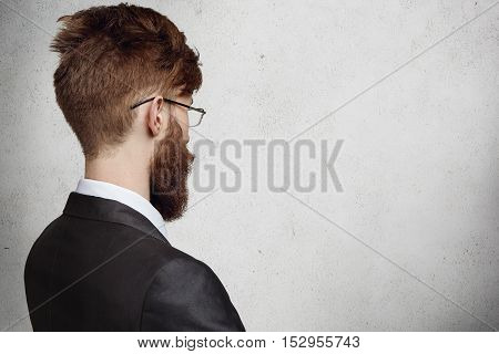 Rear View Of Stylish Young Businessman In Spectacles Standing In Office And Looking At Blank Wall Wi