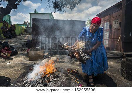 Chichicastenango Guatemala - April 24 2014: Maya woman performing a traditional mayan ritual in the cemetery of the town of Chichicastenango in Guatemala