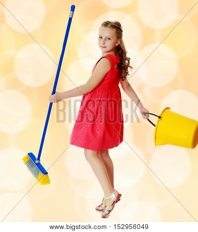 Beautiful little girl in a red short dress with a bucket and brush pleasure to cleans the house.Brown festive, Christmas background with white snowflakes, circles.