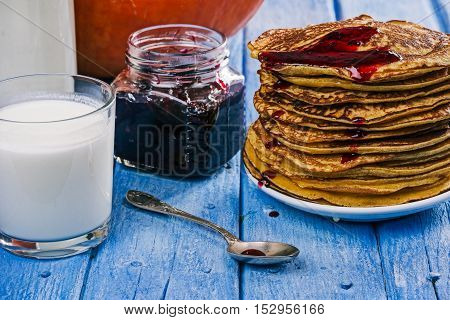 Stack of prepared pumpkin pancakes and blackcurrant jam for halloween party