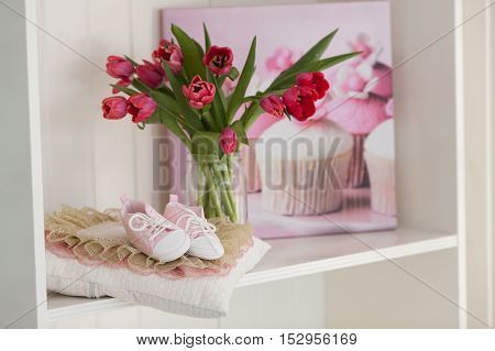 Pink children's shoes and tulips. Room for the little girl. Waiting for the baby. Pink background.