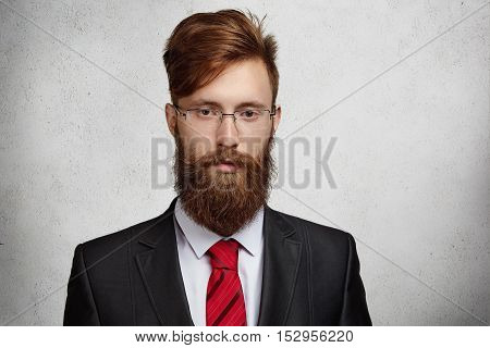 Close Up Shot Of Attractive Young Bearded Corporate Worker In Spectacles And Elegant Suit On His Fir