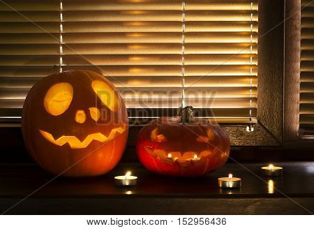 Halloween pumpkin with candles on the windowsill