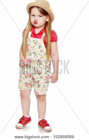 Portrait of funny little girl with long flowing blond hair to her waist. The girl pouted. In a hat and shorts , the girl is holding a Popsicle - Isolated on white background