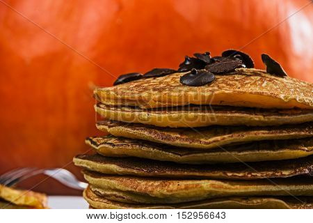 Stack of prepared pumpkin pancakes with chocolate drops on the big orange pumpkin background