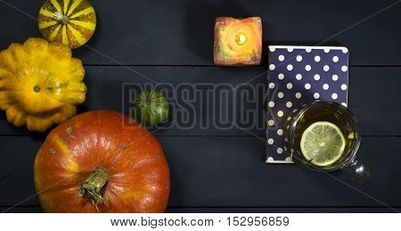 A cup of tea pumpkin squash and notebook on blue wooden table