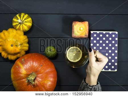 Tea cup in a female hand on the background of the table with pumpkins a book and notepad
