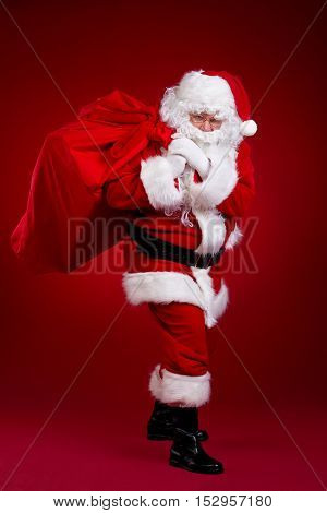 Santa Claus comes with a big bag of gifts. Full length portrait.