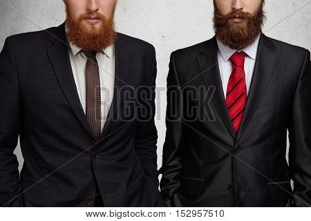 Cropped shot of two Caucasian bearded entrepreneurs dressed in formal suits standing with hands in pockets during business meeting in office. Two young colleagues or partners having agreement