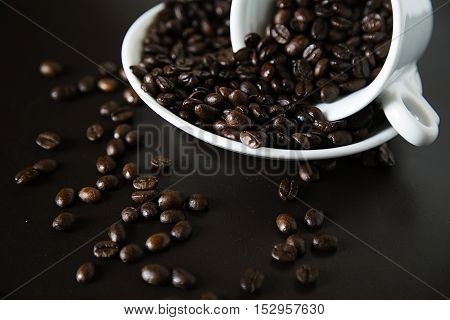 The scattered coffee grains in a cup and a saucer