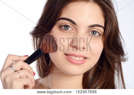 Young beautiful woman applying make up. Isolated white background.