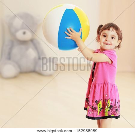 Happy little girl with pigtails on the head , in a pink dress. The girl lifted a large, inflatable striped ball.On blurred background children's room in which sits a large Teddy bear.