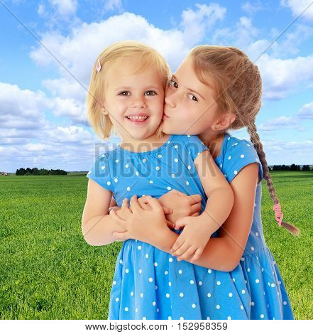 Two charming little girls, sisters , in identical blue dresses with polka dots. Older sister kissing the younger on the cheek.On the background of green grass and blue sky with clouds.