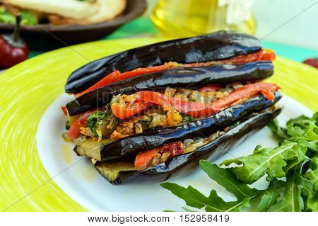 Baked eggplant slices stuffed with vegetables. Satisfying vegan dish. Close up