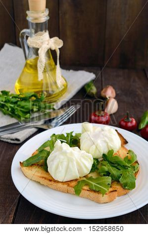 Boiled eggs in a pouch (poached) on crispy toast and green arugula leaves. Dietary breakfast.