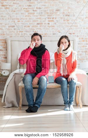 Unpleasant disease. Tired unhappy young couple sitting in the bedroom and wiping their noses while having flu