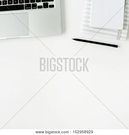 Flat lay home office workspace with laptop diary and headphones on white background.