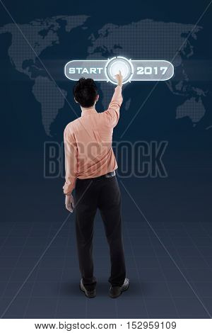 Rear view of a male worker pressing a virtual start button with numbers 2017 and world map on the futuristic screen