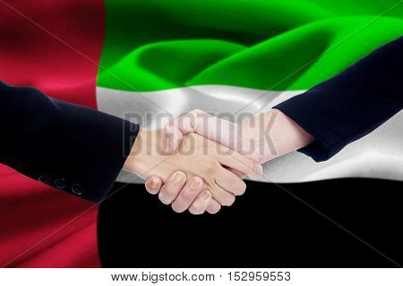 Portrait of two business people handshake in front of the United Arab Emirates flag
