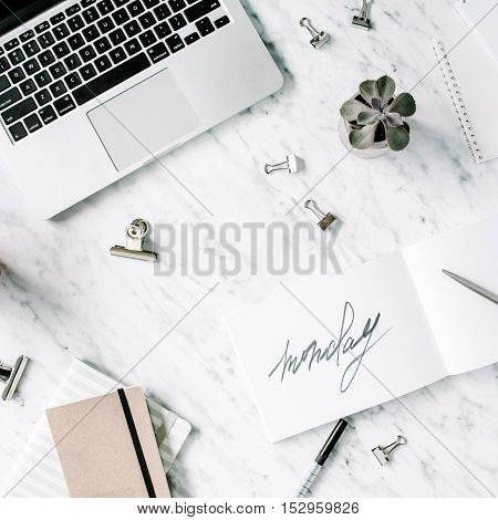 Word monday. Flat lay top view office table desk. Workspace with laptop diary succulent and clips on marble background.