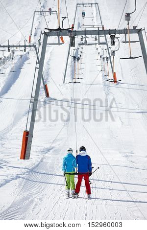 Young couple lifting to the mountain at ski resort
