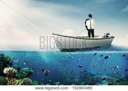 Image of a male entrepreneur standing on the boat while wearing goggles at the sea