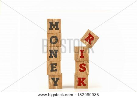 Money and Risk word written on cube shape wooden surface isolated on white background.