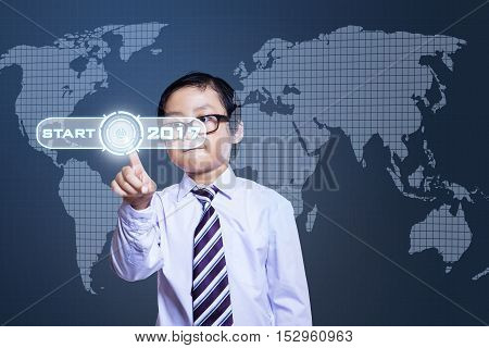 Little boy pressing a start button with numbers 2017 and world map on the virtual screen