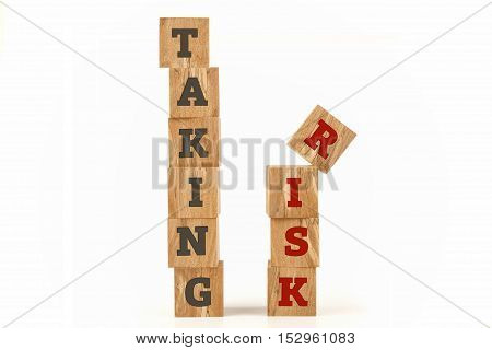 Taking Risk word written on cube shape wooden surface isolated on white background.