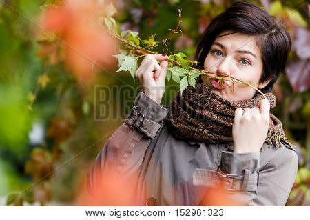 Cheerful cute young brunette woman posing with twig tree. Portrait with autumn mood