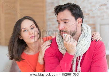 Difficult period. Sad cheerless young man sitting near his girlfriend and holding a paper tissue while being sick