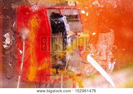 Demolished and vandalized public phone booth on street with graffiti spray marks and stains selective focus