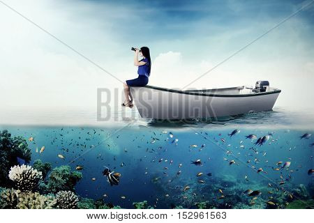 Image of a female entrepreneur looking through binoculars while sitting on a boat at the sea