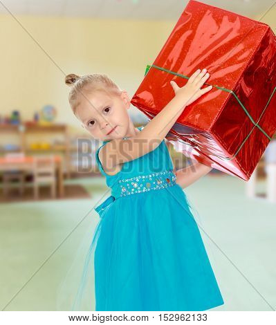 Caucasian little girl in a blue dress, holding the hands of the big red box that is a gift.The girl lifted the box over his head.The concept of pre-school education of the child among their peers