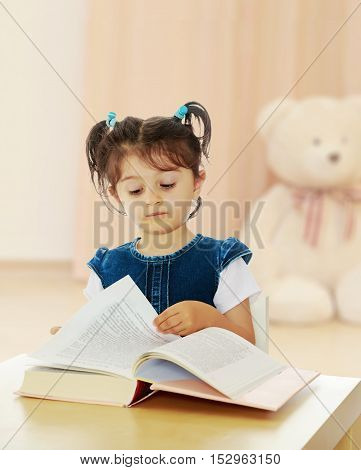Pretty little girl in blue denim dress reading a book sitting at the table.In the children's room in which sits a Teddy bear.