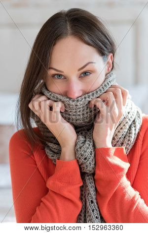 Wearing a warm scarf. Beautiful nice ill woman wearing a scarf and looking at you while having flu