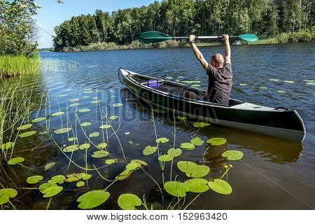 A man swims on a kayak on the lake in summer Sunny day