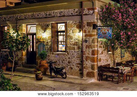 PALEOCHORA, CRETE, GREECE - JUNE 2016: Night view of traditional greek tavern in Paleochora town on Crete island