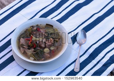 Duck breast soup with organic basil spice, portabella mushrooms, cilantro, red jalapeno pepper, green Chinese bok choy, green onion and ginger on a white and blue cloth on a rustic wood farm table.