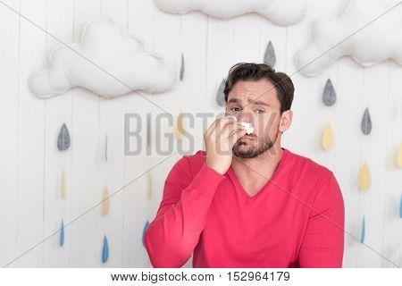 Unpleasant illness. Unhappy depressed young man standing against the rainy background and wiping his nose with a tissue while feeling unwell