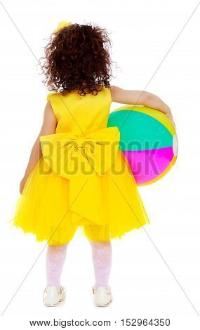 Very small curly-haired girl in bright yellow dress with a huge bow , turned her back to the camera. Girl holding under one arm the ball.Isolated on white background.