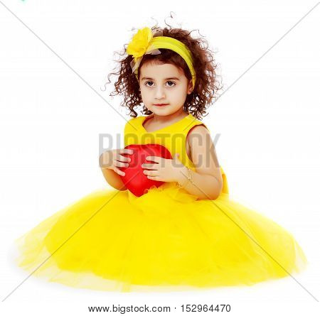 Happy little curly girl in a bright yellow elegant dress sitting on the floor. Girl holding in hand heart.Isolated on white background.
