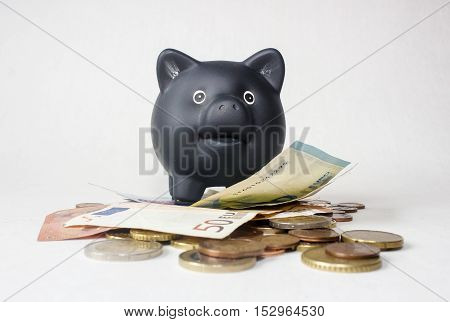 Black smiley pig savings bank with euro money on a white background.