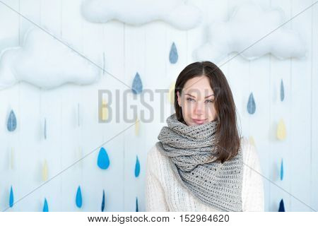 I am in warmth. Good looking delighted young woman wearing a warm scarf and smiling while standing against the rainy background