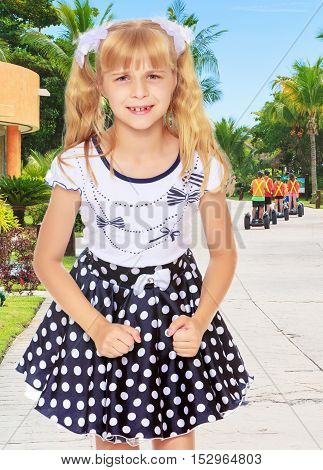 Beautiful little blonde girl in polka dot dress, the girl upset. Close-up.On the background of the road on which the tourists leave.