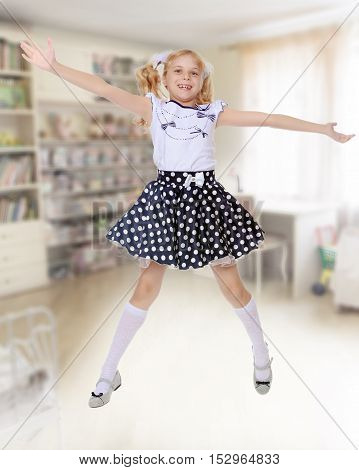 Happy little girl in the short polka-dot dress jumps , spread wide his arms and legs.In the background children's room where there are shelves with books and toys.