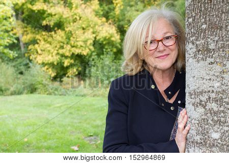 Elegant And Mature Woman Leaning Against Tree Trunk