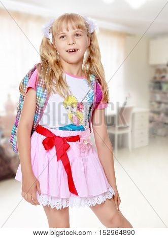 Happy little girl in a pink short skirt with a knapsack on his shoulders. Close-up.In the background children's room where there are shelves with books and toys.