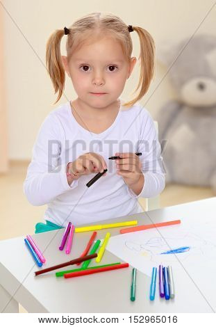 Beautiful little blonde girl with white t-shirts without a pattern, draws markers at the table on a white sheet of paper. The girl is holding a pen . close-up.