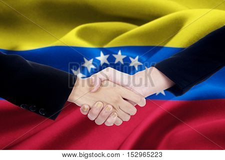 Portrait of dealing handshake with two entrepreneurs closing a conference in front of Venezuela flag